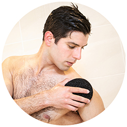 Man washing in the shower with a Ramer Sponge