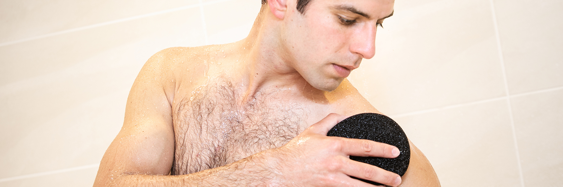 Man in shower using a Ramer Sponge